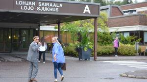 Människor går in via huvudingången till Lojo sjukhus.