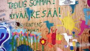 Bilder målade av barn på en vägg.