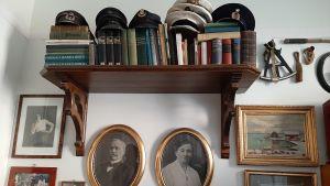 gamla fotografier i ramar och böcker och kaptenshattar på hylla
