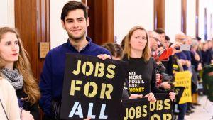 """Aktivister håller upp skyltar med orden """"Jobs For All"""" - Jobb för alla."""