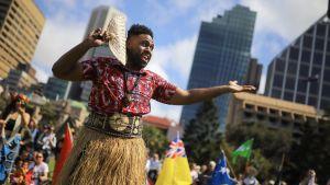 Man klädd i traditionell dräkt gestikulerar under klimatstrejk i Sydney.