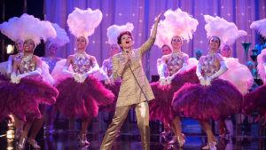 Judy Garland (Renée Zellweger står på scenen och sjunger, runtom en massa showgirls i fjäderkreationer.