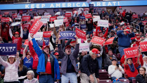"""En bild på massa människor som ropar och håller i plakat där det står """"Trump Pence"""". Plakaten är röda, blåa och vita."""