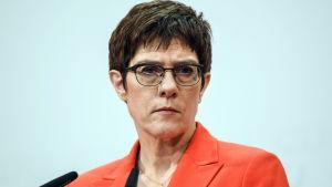 Annegret Kramp-Karrenbauer med sammanbiten min framför en mikrofon under en presskonferens. Hon har en röd kavaj på sig och glasögon med svarta bågar.