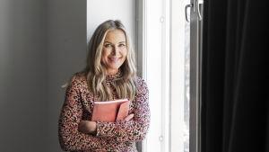 Anne Hietanen sitter på en fönsterkarm.