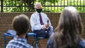 Joe Biden sitter på en stol och blir intervjuad. Han bär ansiktsskydd.