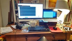 Gammalt skrivbord av trä belamrat med flera datorskärmar och teknisk utrustning för distansarbete hemifrån.