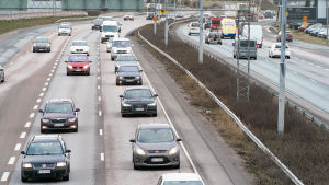 Personbilar i flera filer på en livlig trafikerad ringväg.