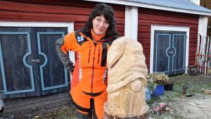 Konstnären Ulla Haglun lutar sig mot sin skapelse, en träskulptur-tomte.