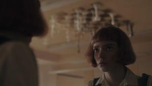 En ung kvinna tittar upp i taket. Där finns ett schackbräde med schackpjäser på.
