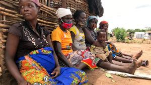Fem kvinnor sitter med ryggarna lutade mot väggen till en enkel hydda. En av kvinnorna har ett litet barn i famnen