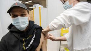 Ung person får coronavaccin i armen. Sjukskötaren Tiina Palm vaccinerar astmatikern Juha Sjögren.