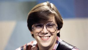 Mikko Alatalo vuonna 1979 Iltalaulu-ohjelman kuvauksissa katsoo kameraan ja hymyilee.