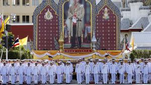 Äldre tjänstemän står utanfär palatset i Bangkok under den kungliga ceremonin.