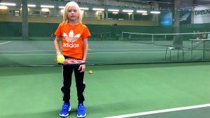 En ung pojke i orange sjokrta håller i en tennisracket och boll.