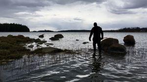 En man går på vattnet bland stenar på en strand.