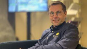 En man med glasögonen sitter i en soffa framför en tv-skärm
