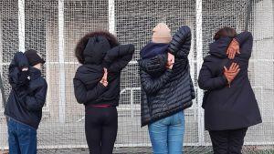 Tre elever ur årskurs 5 och 8 för händerna bakom skulderbladen mot varandra på ryggsidan och redaktören försöker göra samma rörelse.