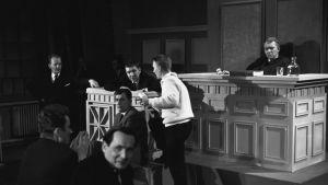 """Sketsiä """"Pertti Masosen yhdestoista hetki"""" kuvataan ohjelmassa Karuselli. Parodia sarjasta """"Perry Mason"""". Oikeussalissa mm. Pentti Siimes, Kauko Helovirta, Sakari Jurkka, Aarre Elo ja Paavo Einiö,"""