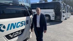 En man i blå kavaj står intill en buss