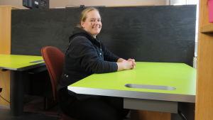 En kvinna sitter vid ett arbetsbord, på en kontorsstol i ett litet kontor tänkt för distansarbetare. Hon ler och ser in i kameran