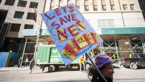 Kvinna håller protestskylt på gatan