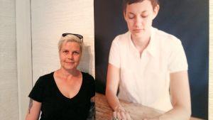 Lisen Sundqvist framför ett av fotografierna i utställningen med Ilar Gunillas bilder i Tobaksmagasinet i Jakobstad.