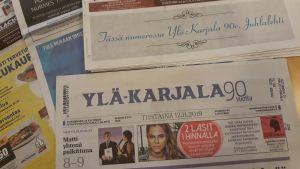 Ylä-Karjala-paikallislehtiä pöydällä.