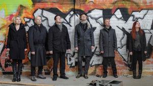 Uusinta Ensemblen muusikot seisovat graffitiseinän edessä yläviistoon katsoen.