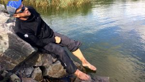 Mikko Peltola uittaa varpaita merivedessä.