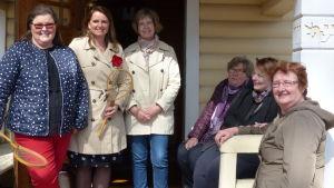MAria Ekman-Kolari, Annika Jansson, Monika Mäkelä, Nina Bergman, Marika Danielsson, Maj-Britt Malmén står och sitter ute på verandan, huvudingången till Villa Mechelin i Bromarv