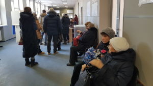Personer står på kö i en vallokal i Ryssland.