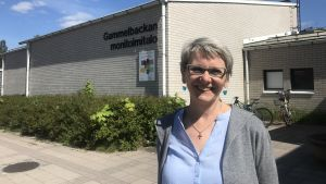 Kvinna står och ler i solen utanför Gammelbacka allaktivitetshus.