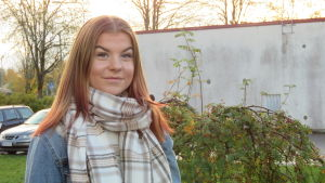 Portättbild på Linn Sjöberg, en tonåring med långt rödblont hår och jeansjacka. Soligt höstväder, lite dis. Kala träd och en grå cementbyggnad i bakgrunden.