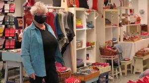 Äldre kvinna med munskydd står vid en hylla med massor av handarbeten och hantverk. Inne i en lokal.