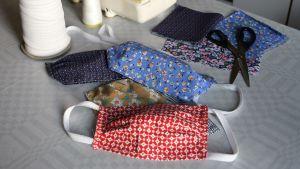 Munskydd av tyg i olika färger och mönster ligger på ett bord bredvid en symaskin.