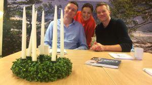 Luciajuryn bestående av Steffen Orsted, Mia Hafrén och Mårten Svartström sitter i ändan på ett bord med en luciakrona på bordet.