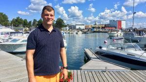 Wilhelm Liljeqvist står vid hamnen i Kasnäs, i bakgrunden syns fiskmjölfabriken.