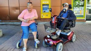 En äldre kvinna och en äldre man utanför en matbutik. Mannen sitter på en elskoter och kvinnan på en rullator.