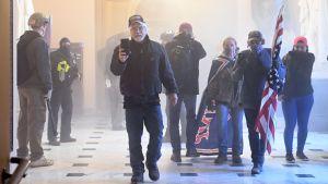 Demonstranter kommer gåendes mot kameran i Kapitolium. En håller upp sin telefon och filmar, andra bär flaggor.