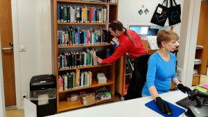 En man står och radar böcker i en bokhylla i ett bibliotek.
