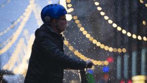 En elsparkcykelåkare med blå hjälm står i skymningen i regn vid Alexandersgatans julbelysning i Helsingfors.