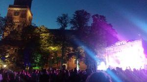 Åbo Domkyrka lyses upp i sommarmörkret av musikfestivalen Down By The Laituris lampor på huvudscenen.