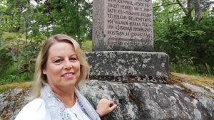 En kvinna med blont halvlångt hår pch ljusa kläder står vid en stor sten där det finns en minnessten.
