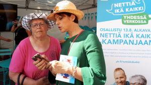 Anna-Liisa Tilus näyttää naiselle jotain kännykältä.