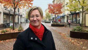 Leende Camilla Gunell framför Torggatans träd i ruskafärger,