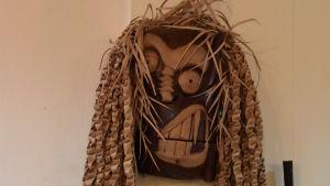 Bild på skulptur i trä som föreställer ett förvridet ansikte.