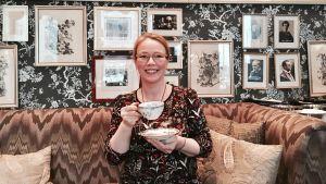 Petra Tandefelt sitter och dricker te på en soffa.