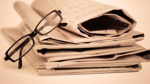 En hög med papperstidningar och ett par svarta glasögon.