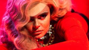 Punasävyinen lähikuva laulaja Erika Vikmanista, jolla on pieniä timantteja kasvoissaan.